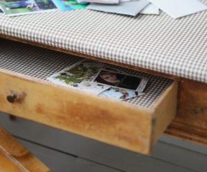Skrivbord där bordsskivan täckts av rutig tapet och skrivbordslådan är utdragen
