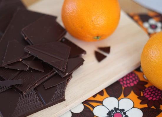 Skärbräda med mörkchoklad som hackas på organgeblommig duk med apelsiner intill.
