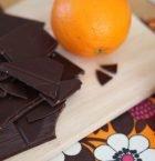 Apelsin och mörk choklad hackad på skärbräda.