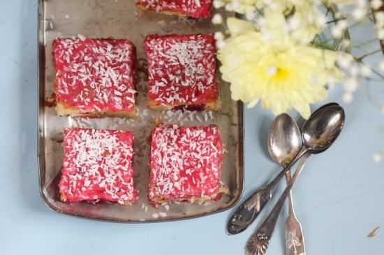Rosa kvadratiska hallonmums med kokosflingor över sig. På sommardukat bord med blommor och silverskedar.