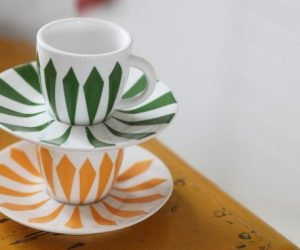 Två färgglada kaffekoppar med dekorerade mönster travade på varandra.