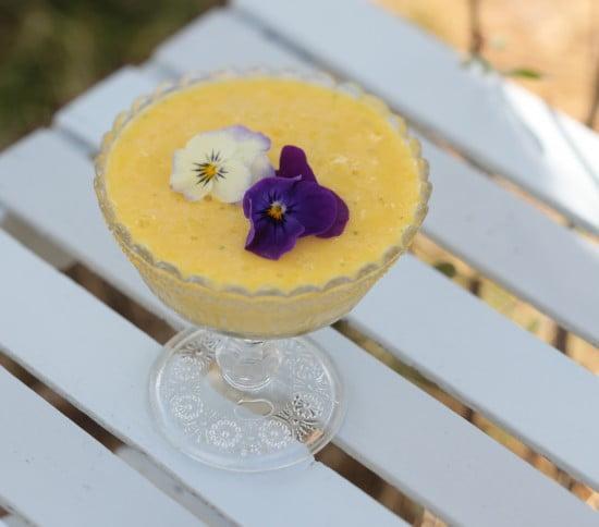 Gul härlig mangoglass dekorerad med vita och blålila blommor. Serveras i glaskål på vitt trädgårdsbord.