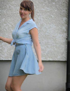 Clara i ljusblå rutig ärmlös topp och ljus kort kjol.