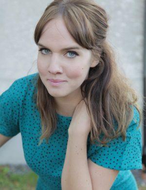 Clara klädd i blågrön klänning med små svarta prickar, tittar in i kameran med uppsatt hår.