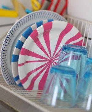 Vita tallrikar som dekorerats med rosa och blå ränder.