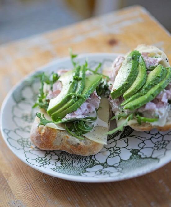 Ljus bröd med skinkröra och skivad avokado på grönblommig tallrik.