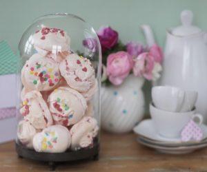 Glasbehållare fullproppad med rosa marängkakor.