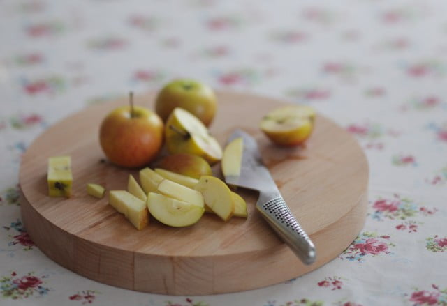 Hackade äpplen på skärbräda.