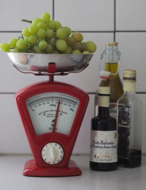 röd gammeldags köksvåg i metall med skålen på toppen fylld med gröna druvor