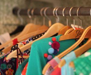 Närbild på trägalgar som hänger tätt med färgglada kvinnoplagg.