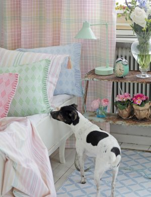 Vit gammal träsoffa bäddad med ljusa pastellfärgade kuddar och lakan, hunden Melker står med nosen i luften redo att hoppa upp i soffan.