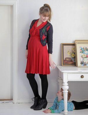 Clara klädd i röd klänning så gravidmagen syns tydligt, vinkar till sonen Bertil som gömmer sig under ett skrivbord intill.