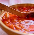 Mustig färgstark soppa i stort soppkärl med träslev.