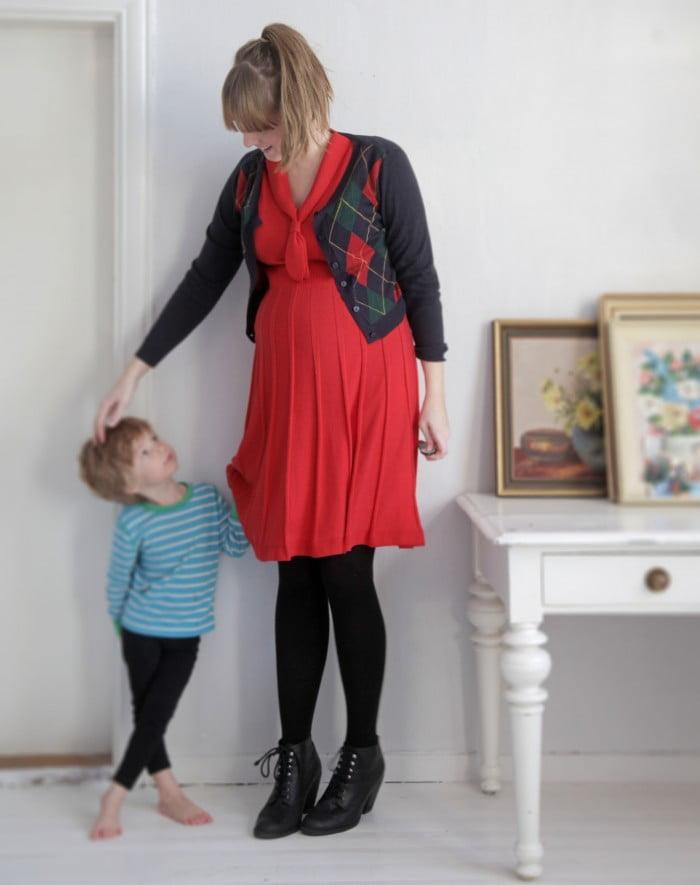 Clara med en av sina söner, själv klädd i röd klänning och kofta.
