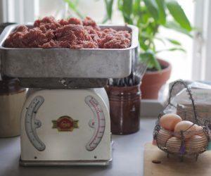 Gammeldags hushållsvåg med köttbitar och intill står en trådkorg med lantägg.