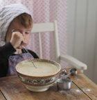 Pojken Bertil vispar pannkakssmet vid köksbordet.