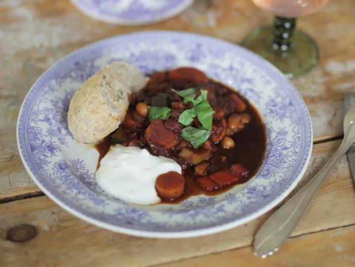 Mörk mustig gryta serveras med ljus bröd på blåvitt porslin.