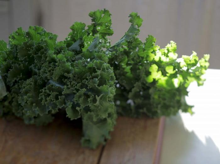 Grön krispig grönkål på skärbräda.