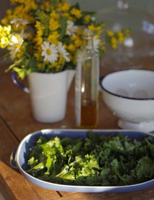 Fat fullt med grönkålsblad på dukat sommarbord.