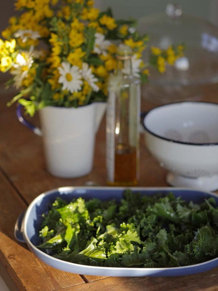 Grönkål i ungsfastform redo för ungen på köksbord med sommarblommor.
