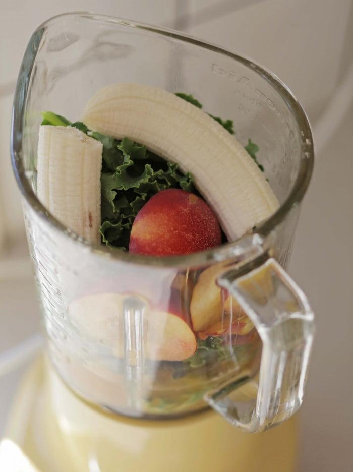 Frukt och grönt i en blenders glaskanna.