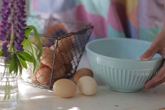 Äggkorg och bakbunke på bordet med sommarens lupiner.