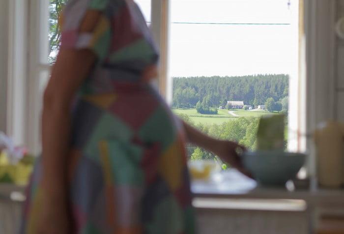 Barnmagen i luften och bakom den skymtar utsikten från arbetsbänken med grönskande åkrar.