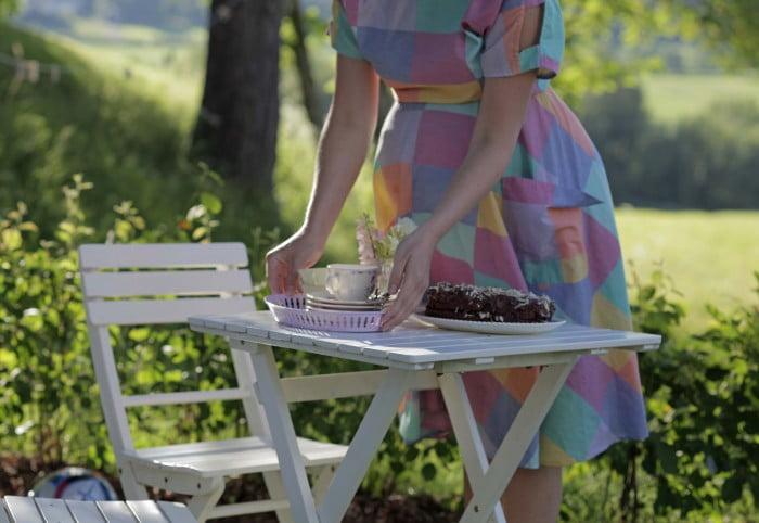 Cafébord utomhus med kaka på fat.
