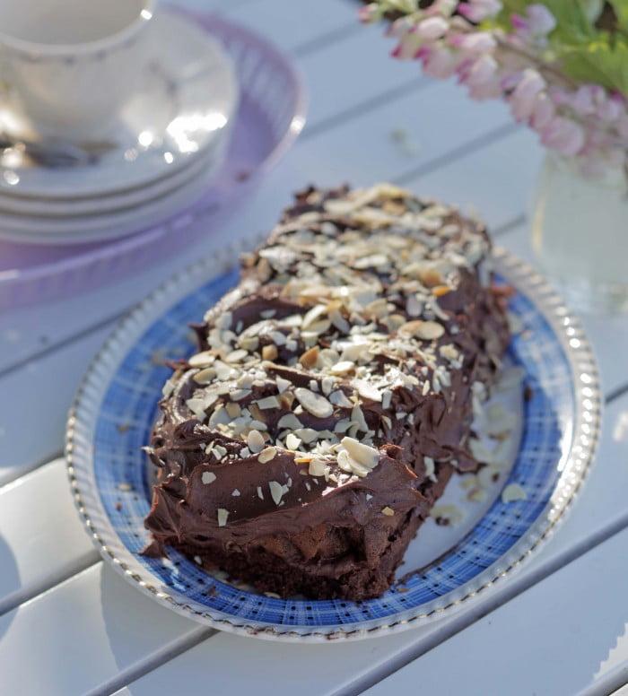 Den mörka färdiga kakan med glänsande glasyr och ljusa mandelspån ovanpå.