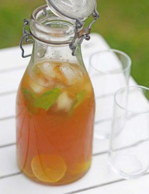 Iste i klar glaskaraff med fruktbitar i teet, karaffen står på ljust trädgårdsbord.