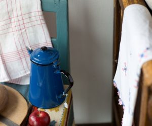 Blå emaljkanna med prislapp på från loppis bland vita secondhanddukar