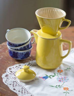 Gul porslinskanna med filtertratt för kaffe och blå koppar dukade på bord.