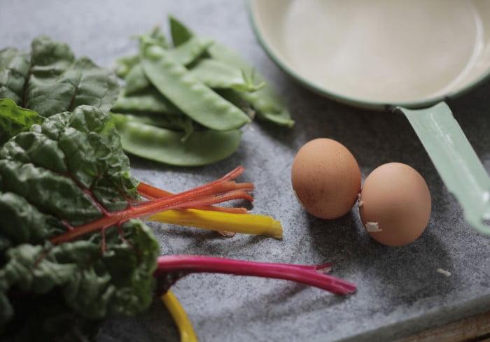Ett par bruna ägg, sockerärtor och röd stjälkar från grön mangold på kökets arbetsbänk.