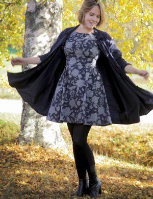 Clara i gråblommig höstklänning snurrar runt så kappan fladdrar i höstsol utomhus