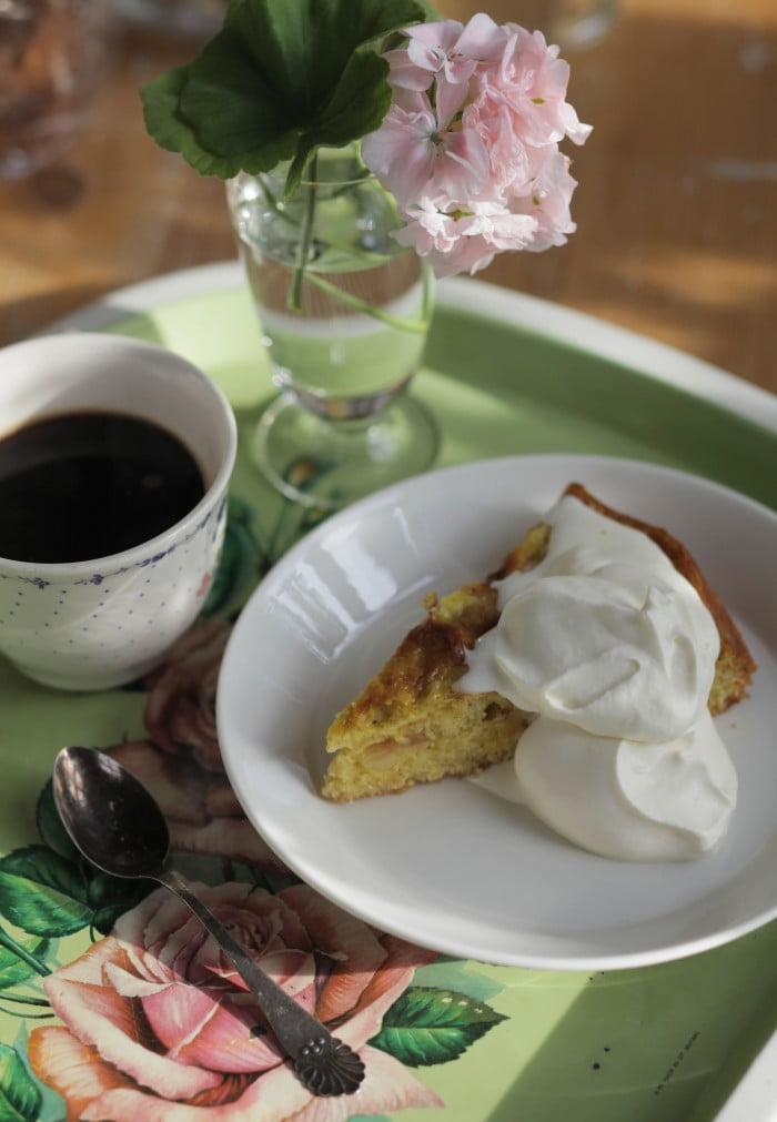En bit äppelpaj och kaffe på kaffebricka med rosor.