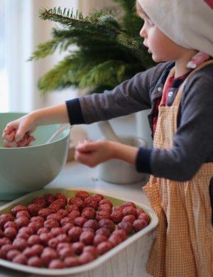 Sonen Bertil klädd i förkläde rullar köttbullar på stort fat i lantkök.