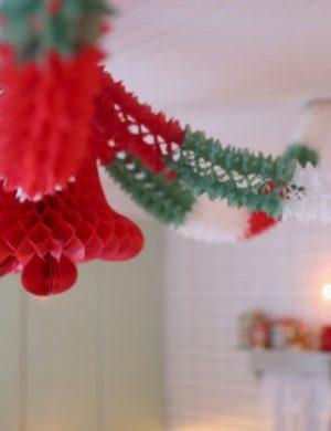 Julgirlander av papper som hänger i taket, rödgröna och vita