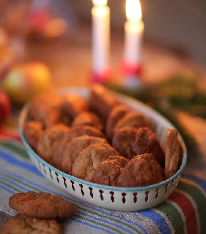 Små runda chokladkakor i rund skål med julljus i bakgrunden.