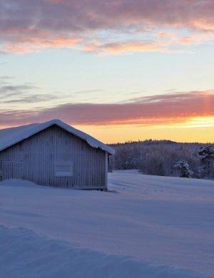 Snöig lada i lantligt landskap med färgad himmel i bakgrunden