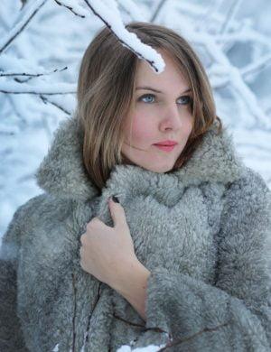 Clara klädd i grå vinterpäls står i kritvitt vinterlandskap och drar kappan närmre kroppen.