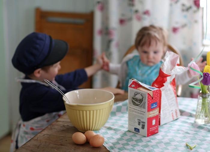 Småbröder med mjölk, mjöl och pannkaksmetens bunke på bordet.