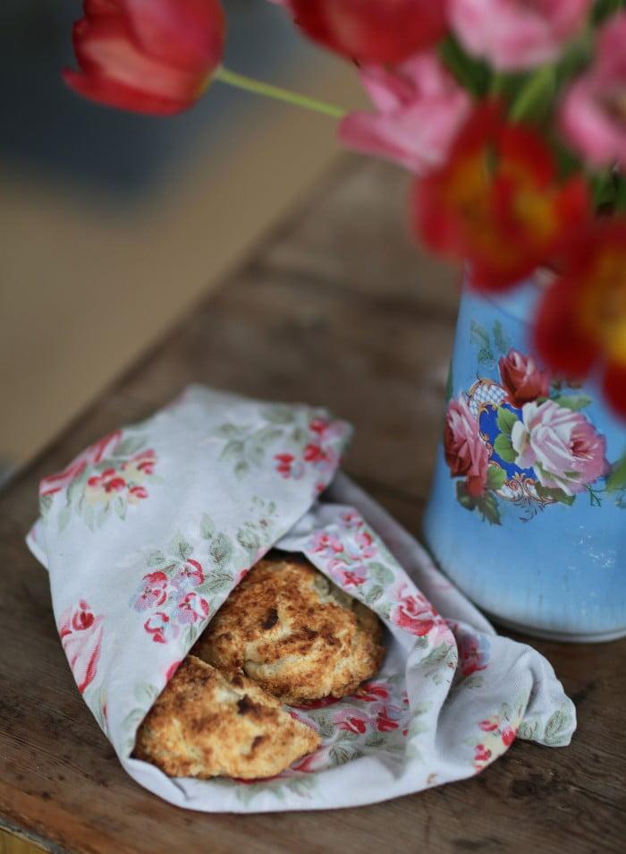Nygräddade scones håller värmen i blommig kökshandduk.