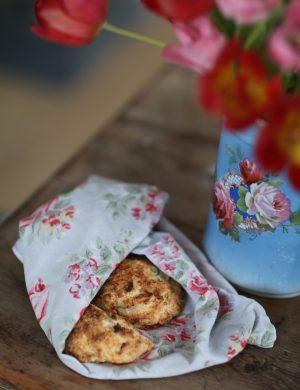 Blommig handduk med nygräddade scones inlindade, står på bord med tulpaner.
