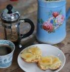 Frukostbord med nygräddade scones på tallrik, kaffekanna, kopp och en blomvas med tulpaner som skymtar.
