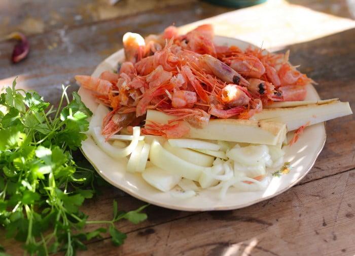 Räkskal på tallrik blir god buljong i sällskap med grönt i kokande gryta.