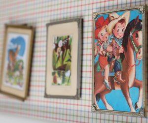 Barntavla med tecknade figurer hänger på vägg i barnrum, till exempel två barn som är cowboys.