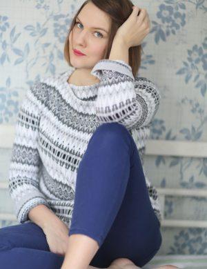 Clara i blå tights och stickad kofta sitter på sofflocket och tittar in i kameran.