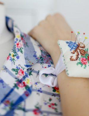Claras hand med en nåldyna som är fastknuten runt handleden.