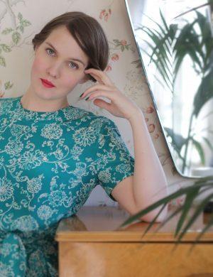 Clara i grönskimrande silkesklänning med vitt mönster i tyget och kort ärm.