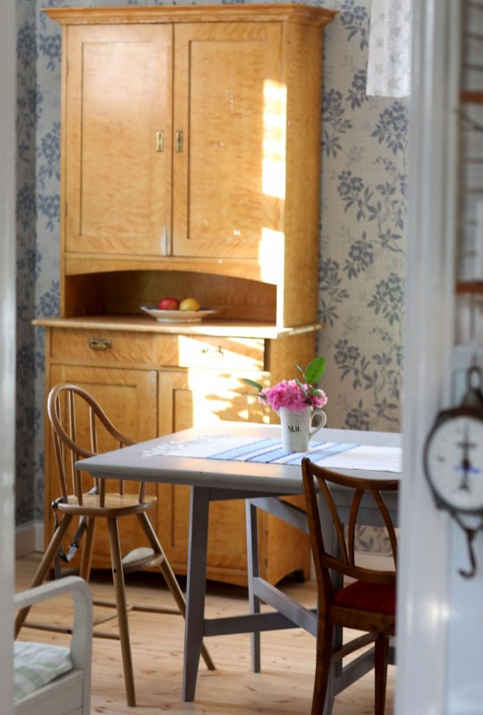 Gult gammaldags skåp i Claras vardagsrum med barnstol framför och blå blommig tapet i bakgrunden.